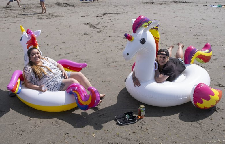 Amy Ridenour, left, and Savannah Smith found the perfect way to enjoy the beach and the low tide at Alki Sunday.  Sunday's low tide made it easy to socially distance along Alki Beach in West Seattle.  Photographed Sunday May 10,2020 213937