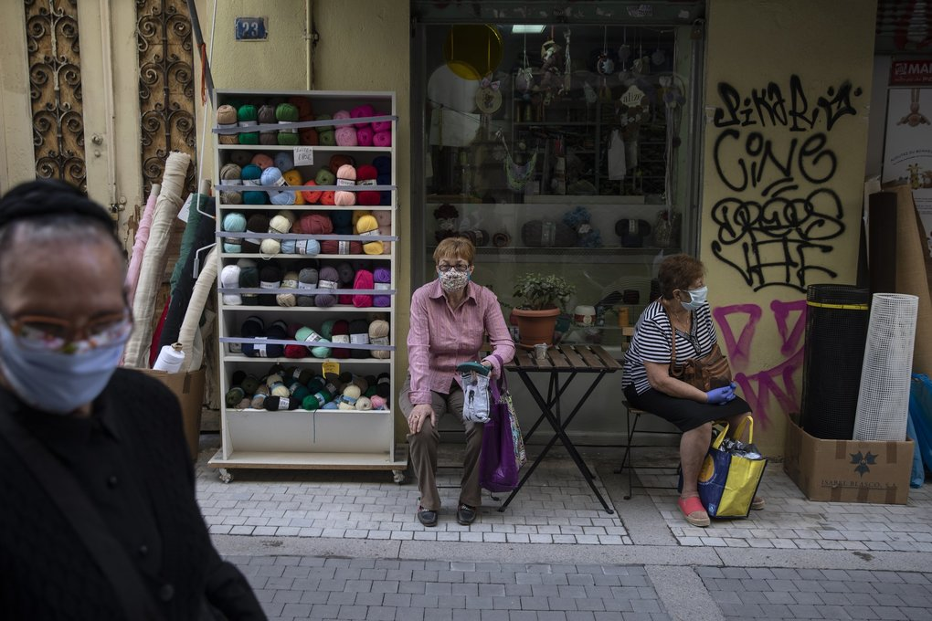 Women wearing masks wait their turn outside a shop that sells yarns and fabrics in central Athens.  Greece has entered the second phase of lifting its lockdown, with all retail stores allowed to reopen and the final grade of high school resuming classes. (Petros Giannakouris / The Associated Press)