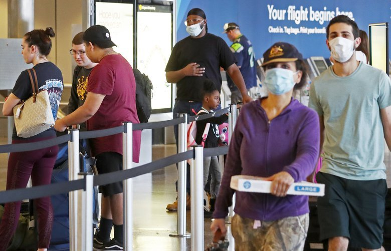 Passengers are seen at Seattle-Tacoma International Airport, Sunday, May 10, 2020 in Seattle during the coronavirus outbreak. The airport is last among major West Coast airports to implement mandatory mask wearing, a formal policy for Sea-Tac airport is still more than a week away and details are yet to be worked out. 213936