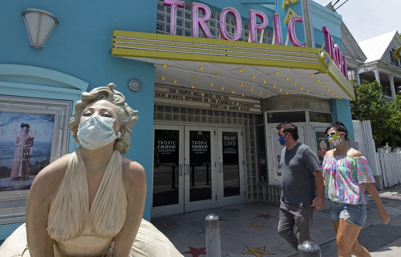 """In this photo provided by the Florida Keys News Bureau, Florida Keys residents David Sloan, second from right, and Heather May Potter, right, approach a life-size sculpture of Marilyn Monroe adorned with a protective mask Sunday, May 3, 2020, in Key West, Fla. """"Forever Marilyn,"""" inspired by a famous photograph of the actress in a white dress with a blowing skirt, was crafted by the late American sculptor J. Seward Johnson and stands outside the island's Tropic Cinema. Johnson, best known for his life-size cast bronzes placed in public settings, was a part-time Key West resident. The Florida Keys aretemporarily closed to visitors because of COVID-19. People in the Keys and in many other parts of the world are being advised to wear masks in public to reduce potential virus transmission. (Rob O'Neal/Florida Keys News Bureau via AP) FLAN103 FLAN103"""