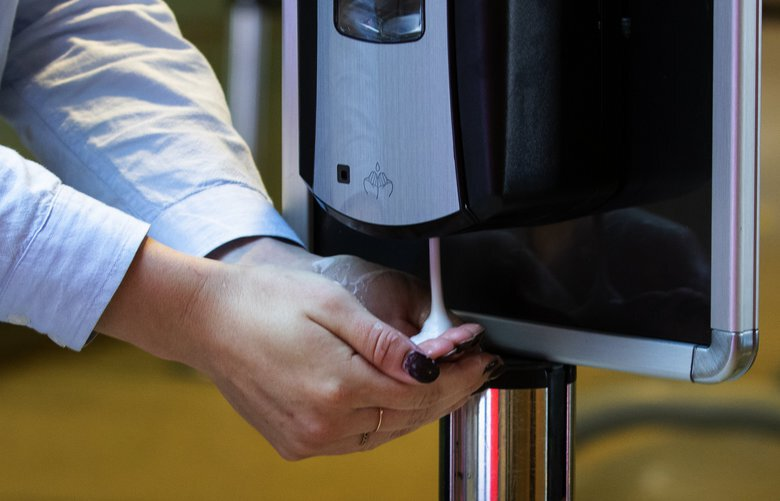 A woman uses hand sanitizer at  Sea-Tac International Airport Friday, May 15, 2020.  240 hand sanitizing stations have been placed all around the airport.  Starting Monday, May 18, the airport will require everyone at the airport to wear masks.   213978