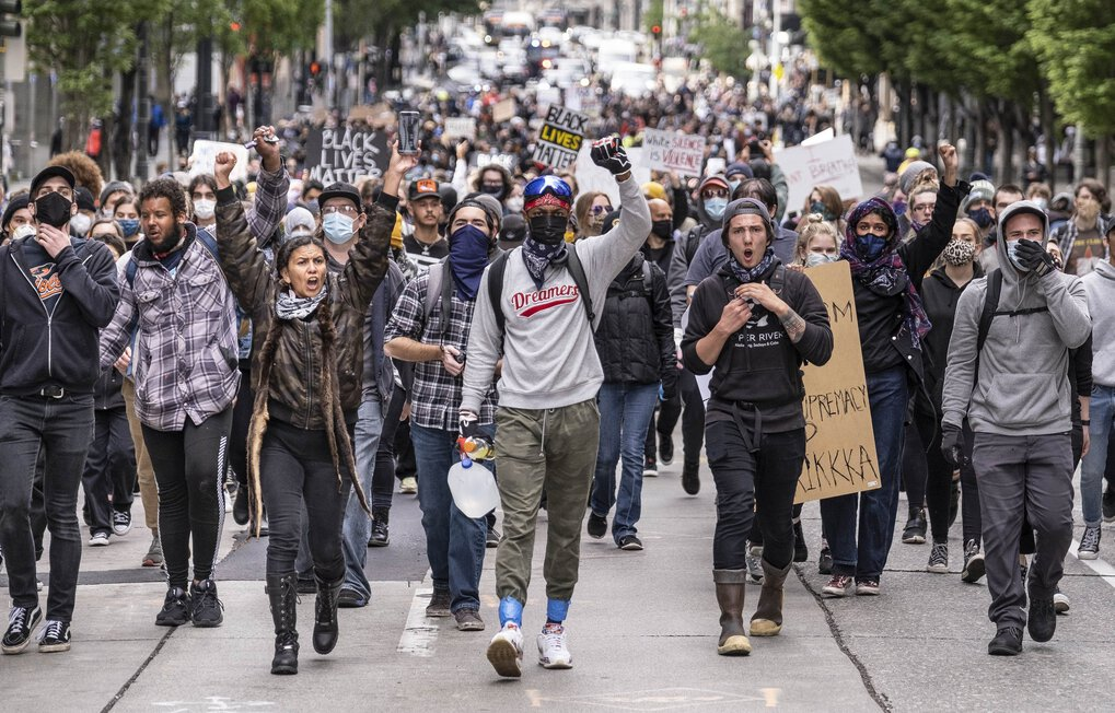 Protesters move south on 2nd Avenue. The day after  Saturday's protest in downtown Seattle began with an army of volunteers determined to wash away the stains of the night before and continued with new demonstrations against police violence. (Dean Rutz / The Seattle Times)