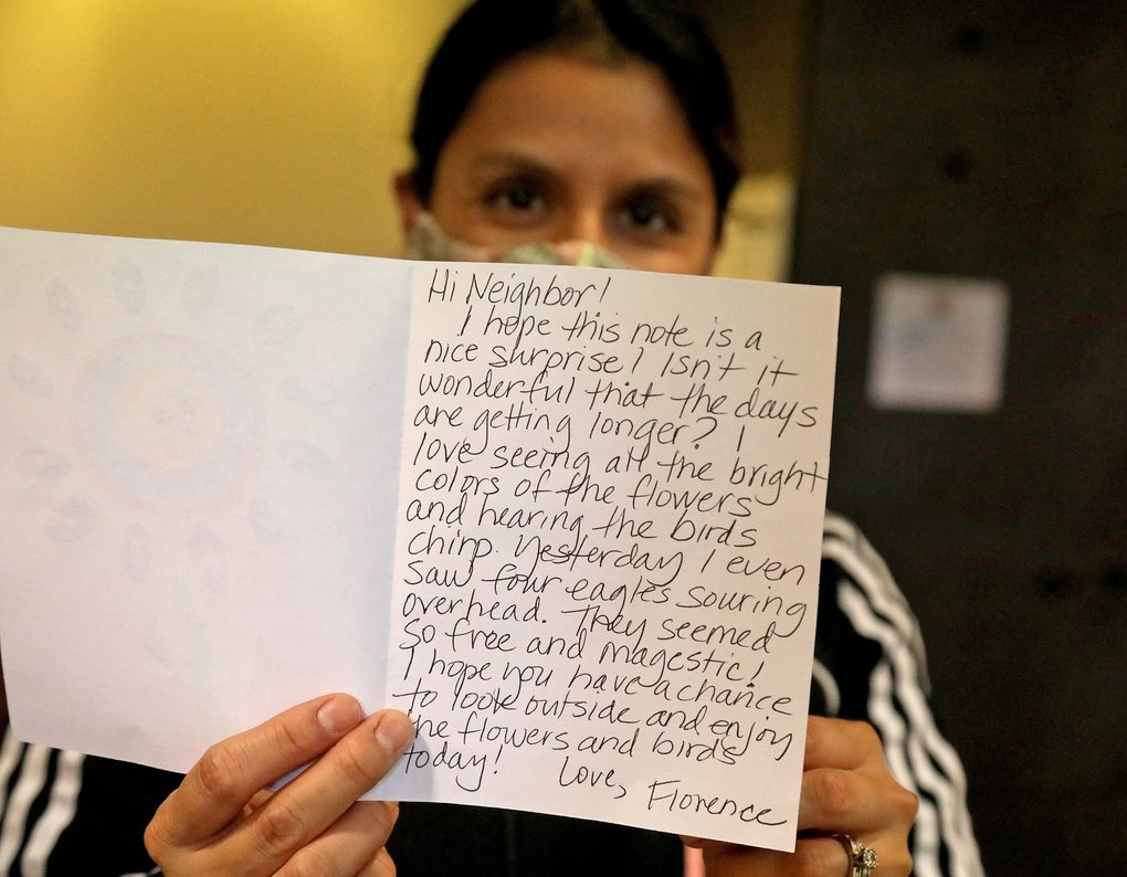 Luz Beas, front desk administrator at the Northshore Senior Center, holds up a volunteer letter writer's handwritten note. (Greg Gilbert / The Seattle Times)