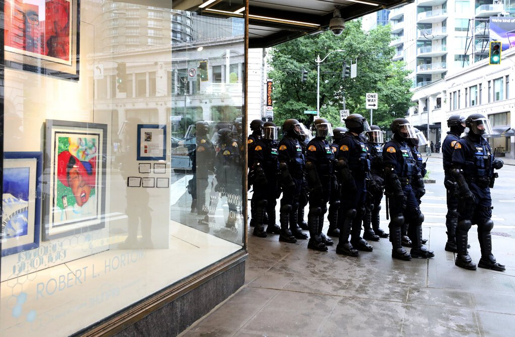 Washington State Patrol members assemble at the corner of the former Macy's store  in downtown Seattle on Saturday. (Alan Berner / The Seattle Times)