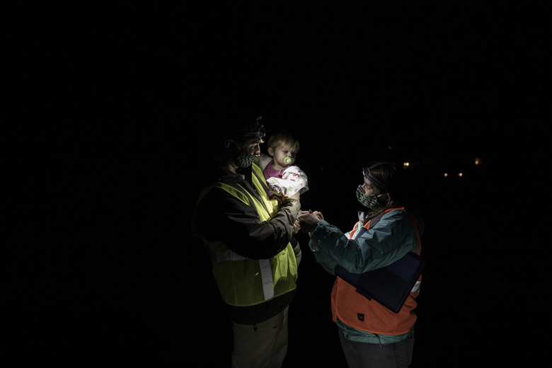 Greg LeClair, who coordinates the Maine Amphibian Migration Monitoring project, with Samantha Grimaldi and their 10-month-old daughter, Audrey, while monitoring amphibian crossings in Unity, Maine, May 1, 2020. Traffic is down, thanks to the pandemic. That's good news for amphibians looking to migrate safely.  (Greta Rybus/The New York Times)