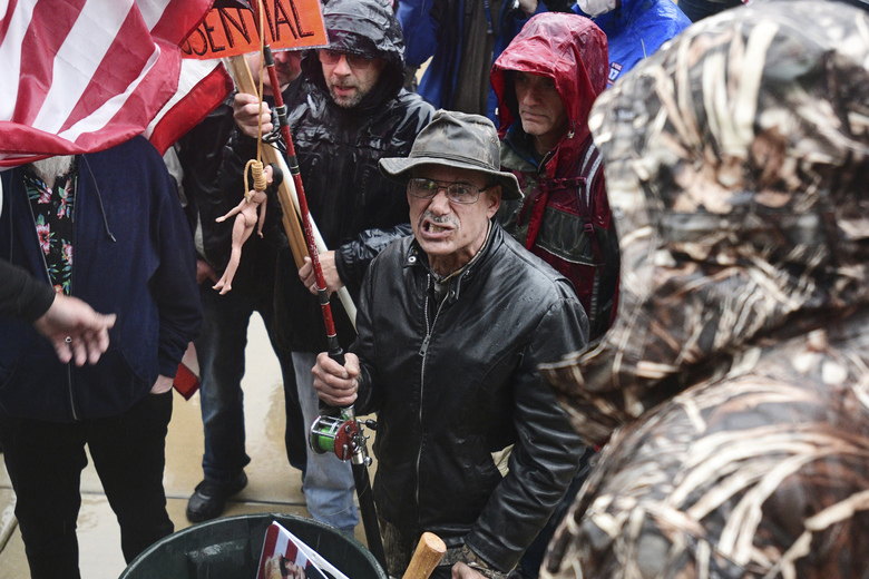 A man with a flag that had a doll with a noose around its neck attached to it grimaces as he comes to the front of the stage during a protest against the state's stay-at-home order at the Michigan Capitol in Lansing, Mich., Thursday, May 14, 2020. (J. Scott Park/Jackson Citizen Patriot via AP)