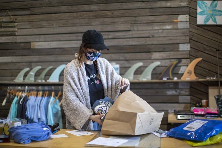 Emma Hamlet prepares orders received online to be picked up at the Long Beach Surf Shop store her family owns, Wednesday, May 27, 2020, in Long Beach, N.Y. Long Island has become the latest region of New York to begin easing restrictions put in place to curb the spread of the coronavirus as it enters the first phase of the state's four-step reopening process. (AP Photo/Mary Altaffer)