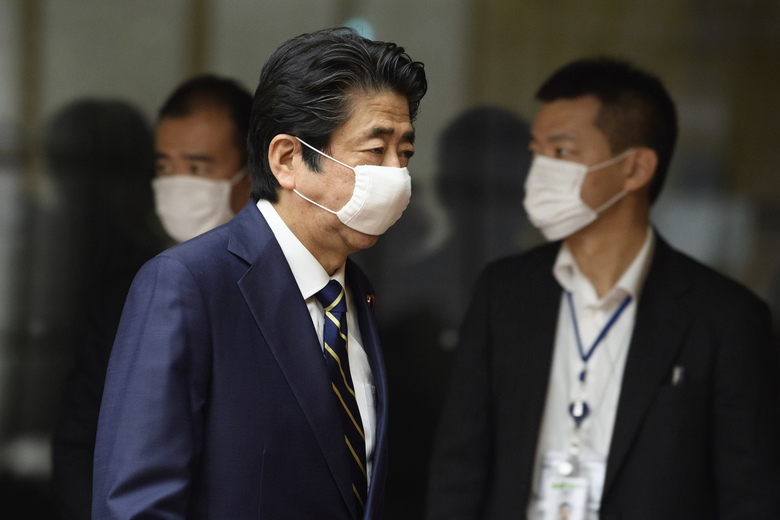 Japanese Prime Minister Shinzo Abe wearing a face mask leaves after a press conference at his official residence in Tokyo Thursday, May 14, 2020. Abe announced the lifting of a coronavirus state of emergency ahead of schedule in most of the country except for eight high-risk areas. (Akio Kon/Pool Photo via AP)