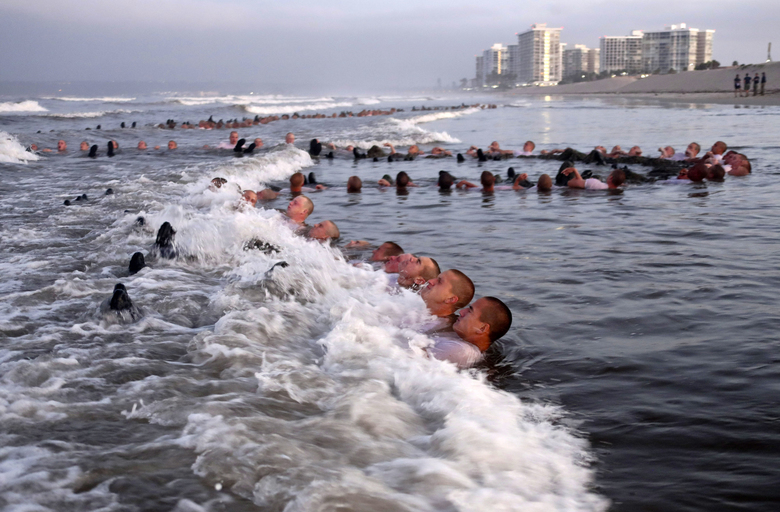 "This Monday May 4, 2020, photo provided by the U.S. Navy shows SEAL candidates participating in ""surf immersion"" during Basic Underwater Demolition/SEAL (BUD/S) training at the Naval Special Warfare (NSW) Center in Coronado, Calif. Navy SEAL recruits and their instructors are being tested for the coronavirus as the candidates in one of the military's most grueling programs return to training with new social distancing guidelines, a top official said Tuesday, May 5, 2020. (MC1 Anthony Walker/U.S. Navy via AP)"