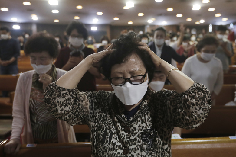A Christian wearing a face mask to help protect against the spread of the new coronavirus prays during a service at the Yoido Full Gospel Church in Seoul, South Korea, Sunday, May 31, 2020. (AP Photo/Ahn Young-joon)