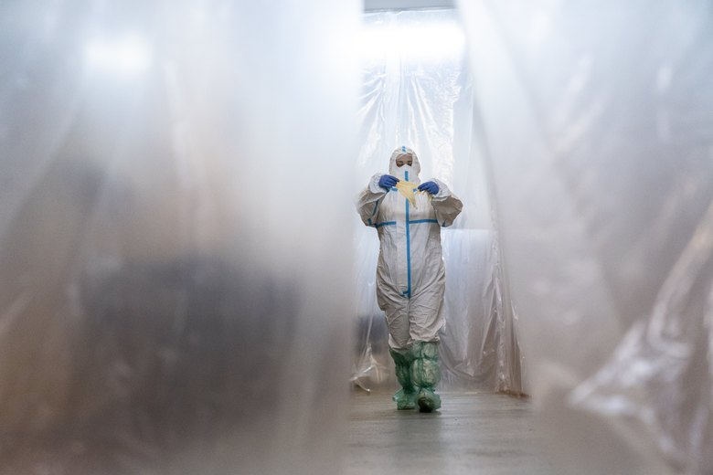 In this photo taken on Monday, May 4, 2020, a doctor, wearing a special suit to protect against coronavirus, walks through a corridor at an intensive care unit at a regional hospital in Chernivtsi, Ukraine. Ukraine's troubled health care system has been overwhelmed by COVID-19, even though it has reported a relatively low number of cases. (AP Photo/Evgeniy Maloletka)