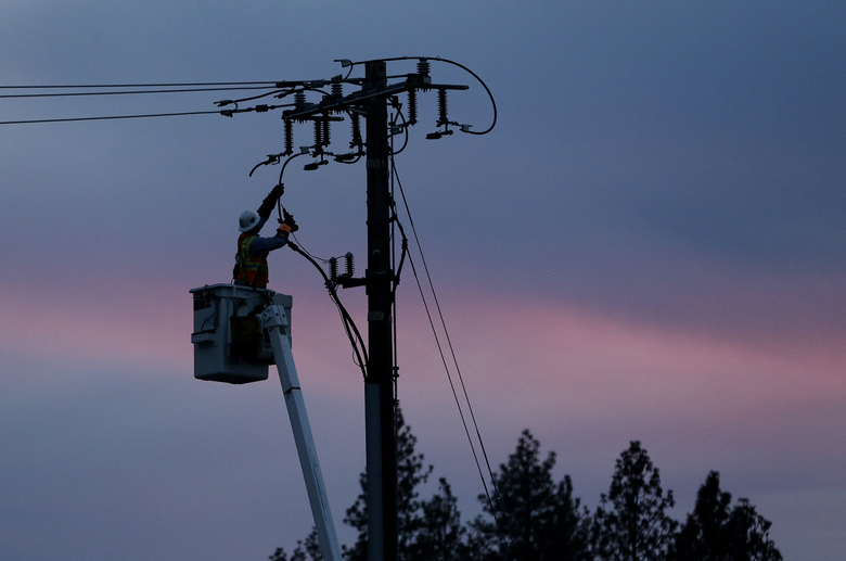 FILE – In this Nov. 26, 2018, file photo, a Pacific Gas & Electric lineman works to repair a power line in fire-ravaged Paradise, Calif. California regulators will consider suspending a $200 million fine against Pacific Gas & Electric for neglecting electrical equipment that killed more than 100 people. If PG&E is granted the waiver to help it emerge from bankruptcy, it will deprive California of desperately needed money as a pandemic-driven recession depletes state revenue from sales and income taxes. (AP Photo/Rich Pedroncelli, File)