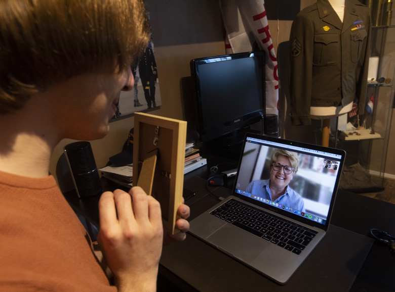 Historian Sebastiaan Vonk, left, shows a picture of Staff Sgt. Maurice Gosney to his niece Kristin Wright, from St. Louis, Missouri, during a Skype talk in Hardinxveld-Giessendam, Netherlands, Monday, May 4, 2020. Gosney, killed in an ambush during WWII near the German village of Sulzfeld on April 11, 1945, is one of more than 10,000 American servicemen and women buried or memorialized at the Netherlands American Cemetery in the southern Netherlands town of Margraten. Vonk's Faces of Margraten project, founded six years ago, already has uncovered some 7,500 photos. They were due to be displayed next to graves in Margraten this week as Europe commemorates the 75th anniversary of the end of World War II, but the event was cancelled due to COVID-19 coronavirus related measures. (AP Photo/Peter Dejong)