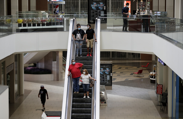 Shoppers wearing face protection ride an escalator at Ingram Park Mall in San Antonio, Friday, May 1, 2020. Texas' stay-at-home orders due to the COVID-19 pandemic have expired and Texas Gov. Greg Abbott has eased restrictions on many businesses that have now opened. (AP Photo/Eric Gay)