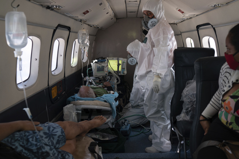 Doctor Daniel Siqueira, center, and nurse Janete Vieira monitor COVID-19 patients onboard an aircraft as they are transferred from Santo Antonio do Iça to a hospital in Manaus, Brazil, Tuesday, May 19, 2020. (AP Photo/Felipe Dana)