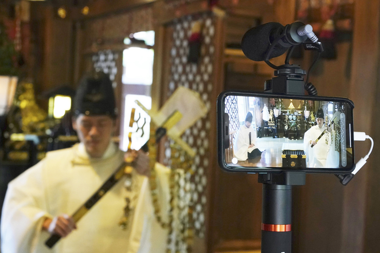 """In this May 8, 2020, photo, Ryoki Ono, head priest, performs a livestream prayer during a 10-day trial of """"online shrine"""" visit program at Onoterusaki Shrine in downtown Tokyo, allowing its visitors to join rituals from their homes. The shrine also accepted from worshipers their prayer messages, which were printed on a virtual wooden tablet each and offered to the Shinto gods to keep away evil spirits and the epidemic. (AP Photo/Eugene Hoshiko)"""
