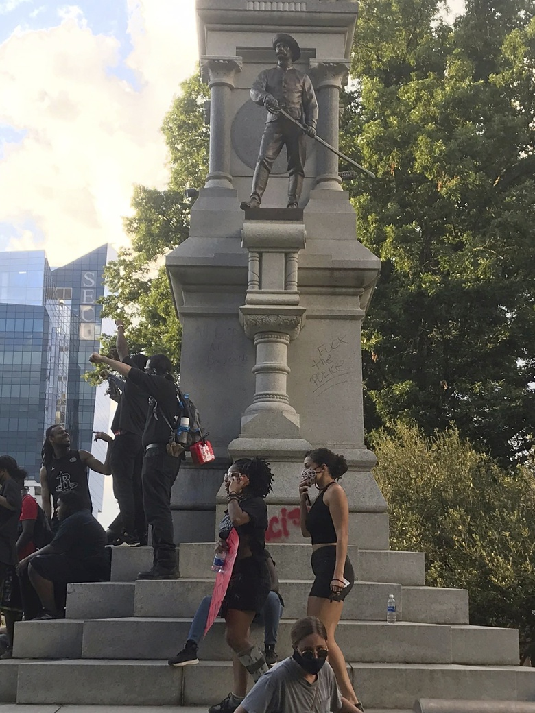 EDS NOTE: OBSCENITY – Protesters gather around the base of the Confederate monument on the grounds of the State Capitol, Saturday, May 30, 2020, in Raleigh, N.C., as people nationwide protested the Memorial Day death of George Floyd, who died in police custody in Minneapolis. (Lucille Sherman/The News & Observer via AP)