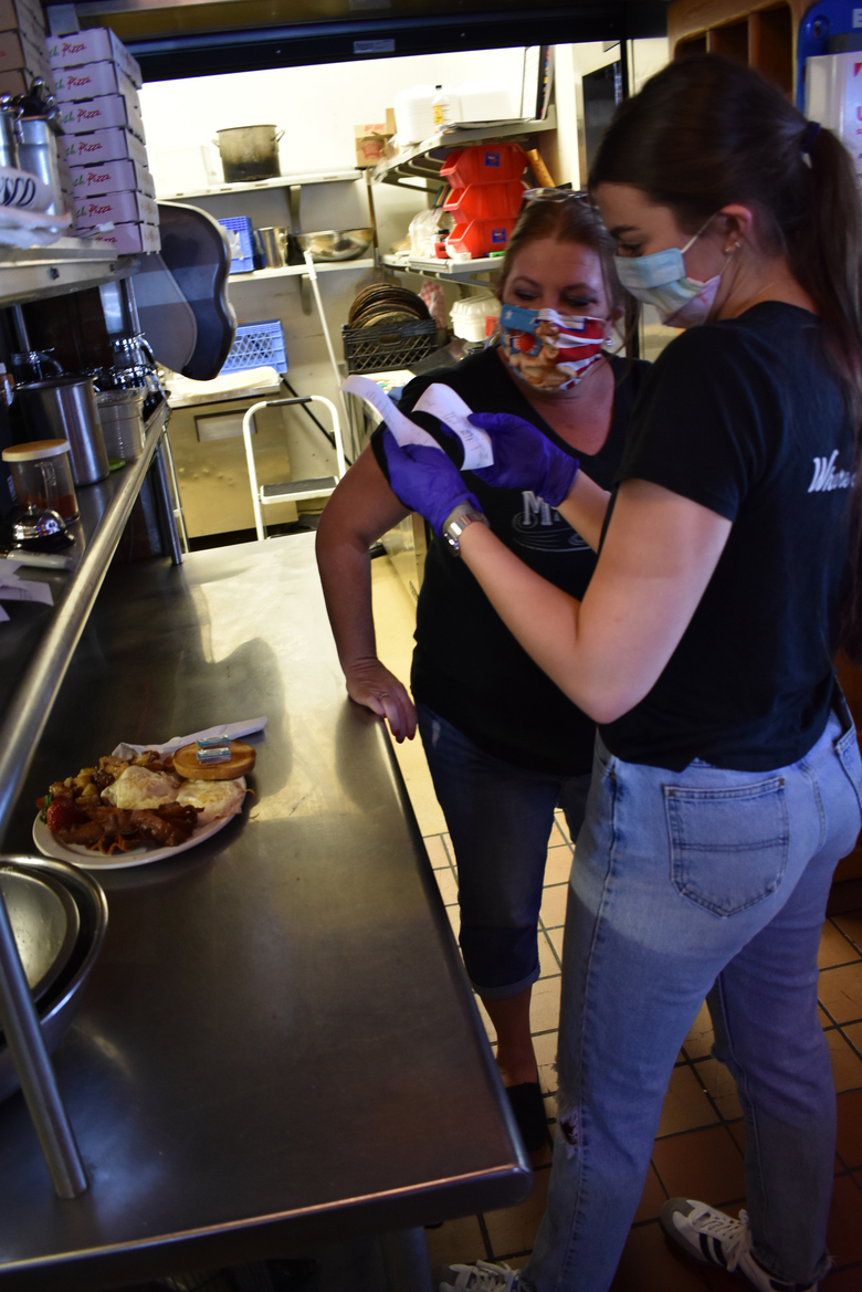 McCormick Cafe manager Charli Perry, left, looks over an order with server Jane Goodridge as the restaurant reopened Monday, May 4, 2020 in Billings, Mont. The state is slowly opening up its economy as some other states extend shutdowns prompted by the coronavirus. (AP Photo/Matthew Brown)