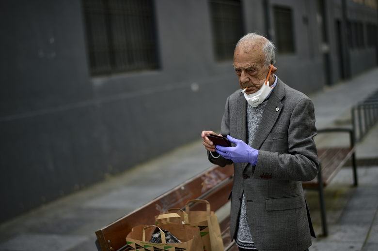 An elderly man partially covers his face with a mask protection to prevent the spread of the coronavirus, as he smokes a cigarette, in Pamplona, northern Spain, Saturday, May 2, 2020. Spain relaxed its lockdown measures Saturday, allowing people of all ages to leave their homes for short walks or exercise for the first time since March 14. (AP Photo/Alvaro Barrientos)