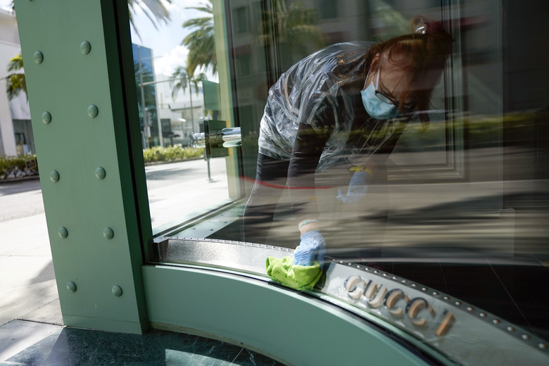 A woman wearing a face mask cleans the front windows of a Gucci store on Rodeo Drive Tuesday, May 19, 2020, in Beverly Hills, Calif. (AP Photo/Ashley Landis)