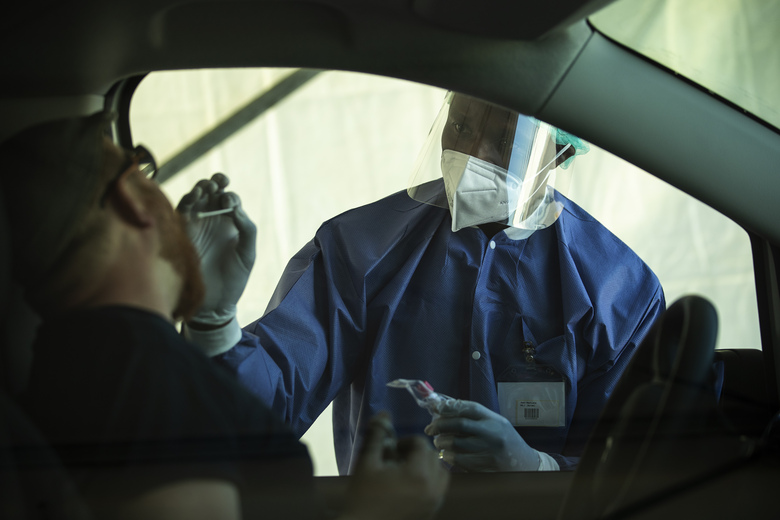 A member of medical personnel, wearing a full protective equipment, takes a mouth swab sample from a man to be tested for coronavirus COVID-19 in a drive-in station in Luxembourg, Wednesday, May 27, 2020. Luxembourg has launch on Wednesday a nationwide coronavirus testing campaign among its population and commuters. (AP Photo/Francisco Seco)