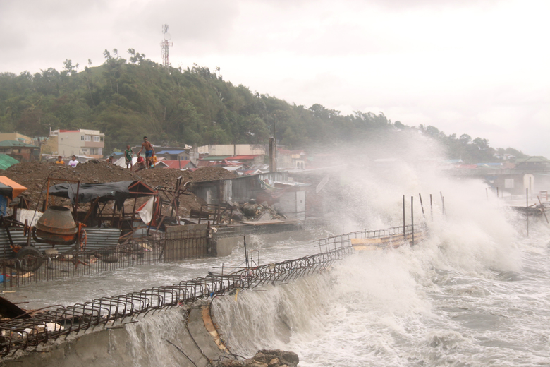 Strong waves batter houses along the coastline of Catbalogan city, Western Samar province, eastern Philippines caused by typhoon Vongfong, Thursday May, 14, 2020. A strong typhoon slammed into the eastern Philippines on Thursday after authorities evacuated tens of thousands of people while trying to avoid the virus risks of overcrowding emergency shelters. (AP Photo/Simvale Sayat)