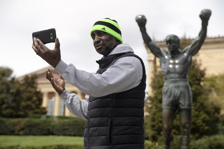 """In this April 3, 2020 photo Xander Hobson makes a video with the Rocky Statue at the Philadelphia Art Museum in Philadelphia. From South Philly to Brazil and  round the globe, an incalculable number of Rocky Balboa fans recreated the run made famous in """"Rocky"""" and duplicated in sequels, spinoffs and Super Bowl spots. """"Rocky"""" finished tied for No. 2 in The Associated Press Top 25 favorite sports movies poll. (AP Photo/Matt Rourke)"""