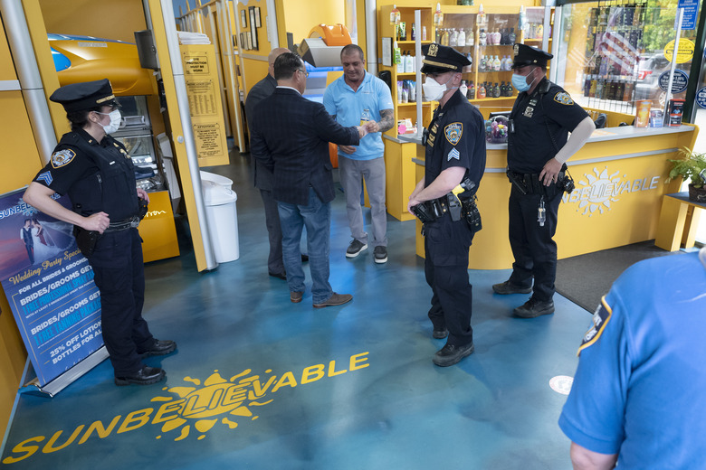 Staten Island tanning salon owner Bobby Catone, center, holds a summons issued to him, Thursday, May 28, 2020, in New York. Catone opened the salon briefly Thursday morning in defiance of a law requiring non-essential businesses to remain closed during the coronavirus pandemic. (AP Photo/Mark Lennihan)