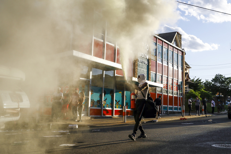 A person shoots a fire extinguisher into the air as he walks though a street in Upper Darby, Pa. on Sunday May 31, 2020, as people move through streets in protest over the death of George Floyd, a black man who was in police custody in Minneapolis. Floyd died after being restrained by Minneapolis police officers on Memorial Day, May 25. (AP Photo/Matt Slocum)