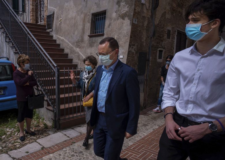 Sabatino Di Girolamo, center, mayor of Roseto degli Abruzzi, with his sister Marisa Di Felice, and with his son Francesco, right, arrives for the funeral of his mother Annunziata, in Montepagano, central Italy, Tuesday, May 12, 2020. Under new regulations imposed by the COVID-19 pandemic only 15 people wearing face masks are allowed to attend funerals inside churches where they have to respect the distancing requirements. (AP Photo/Domenico Stinellis)