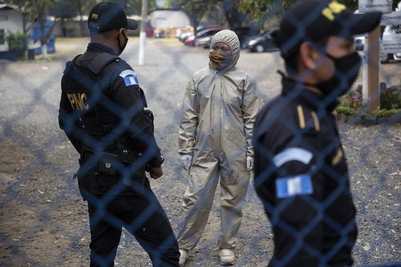 A health worker in protective gear against the new coronavirus, center, talks with a policeman behind a gate at an athletic dorm facility being used to house Guatemalans deported from the U.S. in Guatemala City, Tuesday, April 21, 2020. The recently deported Guatemalans were quarantined in the dorm to wait for new coronavirus test results. (AP Photo/Moises Castillo)