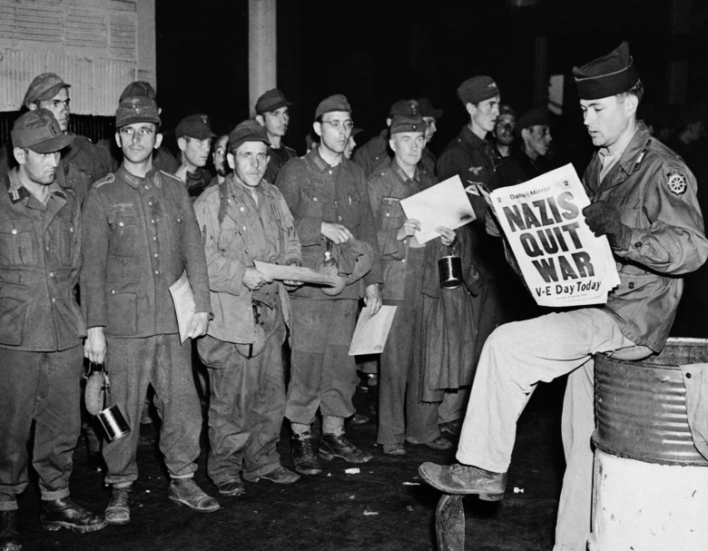 FILE – In this May 8, 1945 file photo Pfc. Clarence K. Ayers of Evansville, Ind., reads the news of VE Day as newly arrived German prisoners stand on a New York City pier. (AP Photo/John Rooney, File)