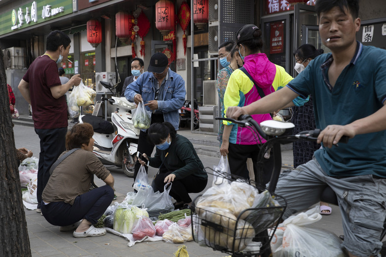 In this Thursday, May 14, 2020, photo, vendors sell vegetable on the streets of Beijing. Factory output rose in April as China's virus-battered economy reopened but job losses depressed consumer spending, a key driver of growth, in a sign of the challenges the ruling Communist Party faces in reviving normal activity. (AP Photo/Ng Han Guan)