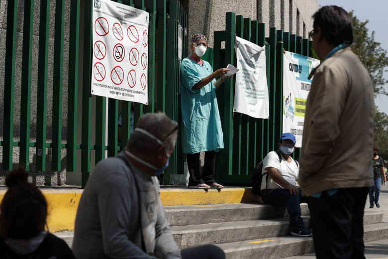 A hospital worker calls out a name from the gate, as relatives of hospitalized patients wait outside in hopes of receiving news of their loved ones, at a public hospital in the Iztapalapa district of Mexico City, Tuesday, May 5, 2020. Iztapalapa has the most confirmed cases of the new coronavirus within Mexico's densely populated capital, itself one of the hardest hit areas of the country with thousands of confirmed cases and around 500 deaths.(AP Photo/Rebecca Blackwell)
