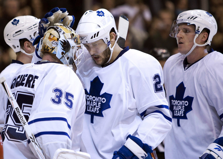 """FILE – In this Feb. 2, 2010, file photo, Toronto Maple Leafs goaltender Jean-Sebastien Giguere, left, is congratulated by teammates Christian Hanson, center, and defenseman Dion Phaneuf, right, after a 3-0 shutout win over the New Jersey Devils in an NHL hockey game in Toronto. The 1977 movie """"Slap Shot"""" was No. 5 in The Associated Press' Top 25 favorite sports movies poll. """"Anybody who's played the game can still relate to it in some capacity because as much as it's changed, a lot of it is still the same,"""" said Christian Hanson, the son of Dave Hanson, who played one of the Hanson brothers in the film, and himself a veteran of 42 NHL games with Toronto between 2008-2011. (Frank Gunn/The Canadian Press via AP, File)"""