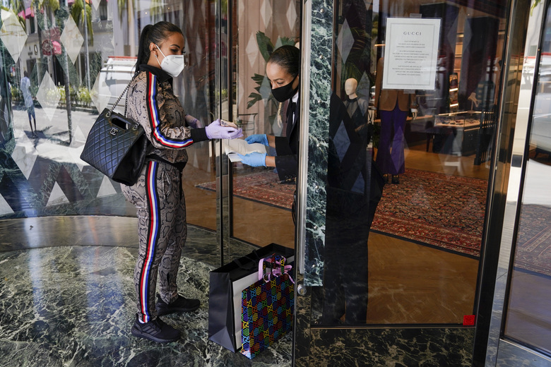 Delicia Cordon receives a purchase from a sales person at Gucci on Rodeo Drive Tuesday, May 19, 2020, in Beverly Hills, Calif. The store is closed for in-store shopping, but offers curbside pickup for orders in advance. (AP Photo/Ashley Landis)