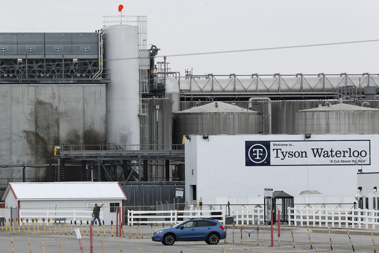 In this Friday, May 1, 2020, photo, a worker leaves the Tyson Foods plant in Waterloo, Iowa. The coronavirus is devastating the nation's meatpacking communities — places like Waterloo and Sioux City in Iowa, Grand Island, Neb., and Worthington, Minn. Within weeks, the outbreaks around slaughterhouses have turned into full-scale disasters. (AP Photo/Charlie Neibergall)