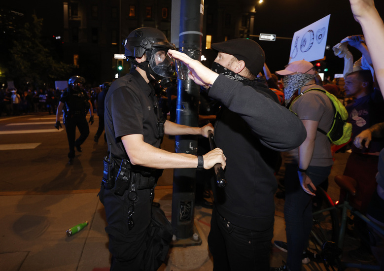 A Denver police officer uses a baton to push back protester outside the State Capitol on Thursday, May 28, 2020, in Denver, during a demonstration over the Monday death of George Floyd in Minneapolis police custody. (AP Photo/David Zalubowski)
