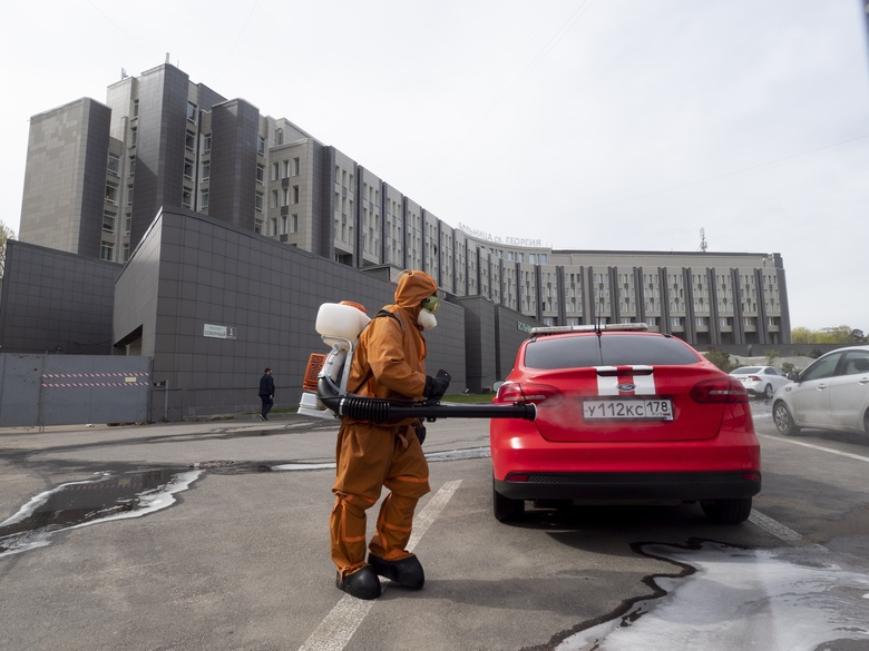 A Russian Emergency Situation worker disinfects a fire department car near the scene of a fire at St. George Hospital in St. Petersburg, Russia, Tuesday, May 12, 2020. A fire at St. George Hospital has killed five coronavirus patients. Russian emergency officials said all five had been put on ventilators. The emergency officials told the state Tass new agency the fire broke out in an intensive care unit and was put out within half an hour. (AP Photo/Dmitry Lovetsky)