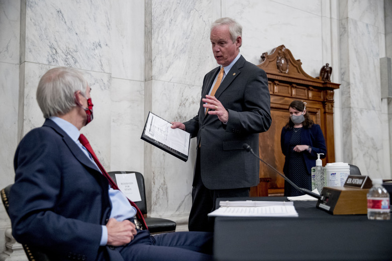Chairman Sen. Ron Johnson, R-Wis., center, speaks with Sen. Rob Portman, R-Ohio, left, at the conclusion of a Senate Homeland Security and Governmental Affairs committee meeting on Capitol Hill in Washington, Wednesday, May 20, 2020, after voting to issue a subpoena to Blue Star Strategies. (AP Photo/Andrew Harnik)