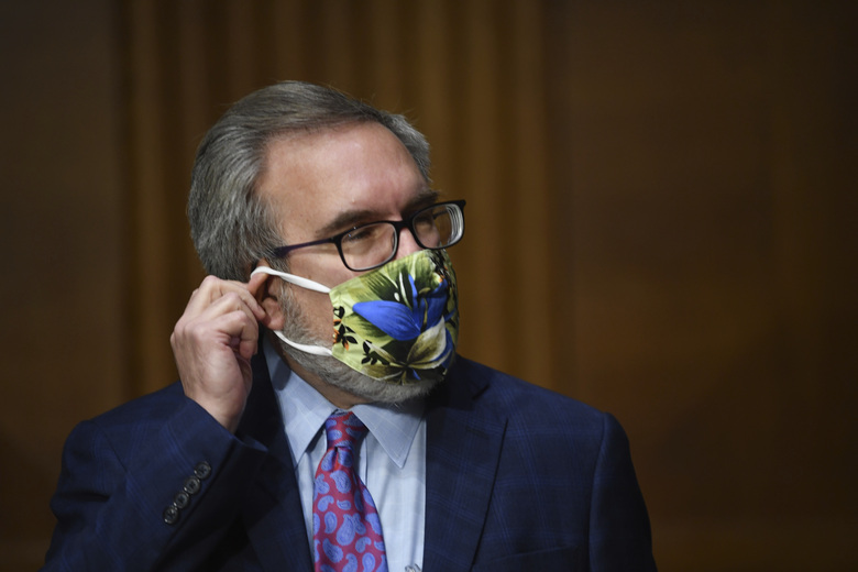 Andrew Wheeler, administrator of the Environmental Protection Agency, adjusts his mask at a hearing during a Senate Environment and Public Works Committee oversight hearing to examine the Environmental Protection Agency, Wednesday, May 20, 2020 on Capitol Hill in Washington. (Kevin Dietsch/Pool via AP)