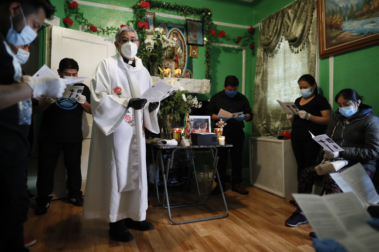 The Rev. Fabian Arias leads a prayer as he performs an in-home service beside the remains of Raul Luis Lopez who died from COVID-19 the previous month, Saturday, May 9, 2020, in the Corona neighborhood of the Queens borough of New York. (AP Photo/John Minchillo)
