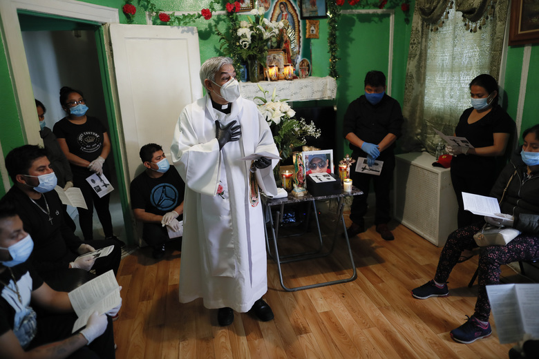 The Rev. Fabian Arias offers a homily as he performs an in-home service beside the remains of Raul Luis Lopez who died from COVID-19 the previous month, Saturday, May 9, 2020, in the Corona neighborhood of the Queens borough of New York. (AP Photo/John Minchillo)