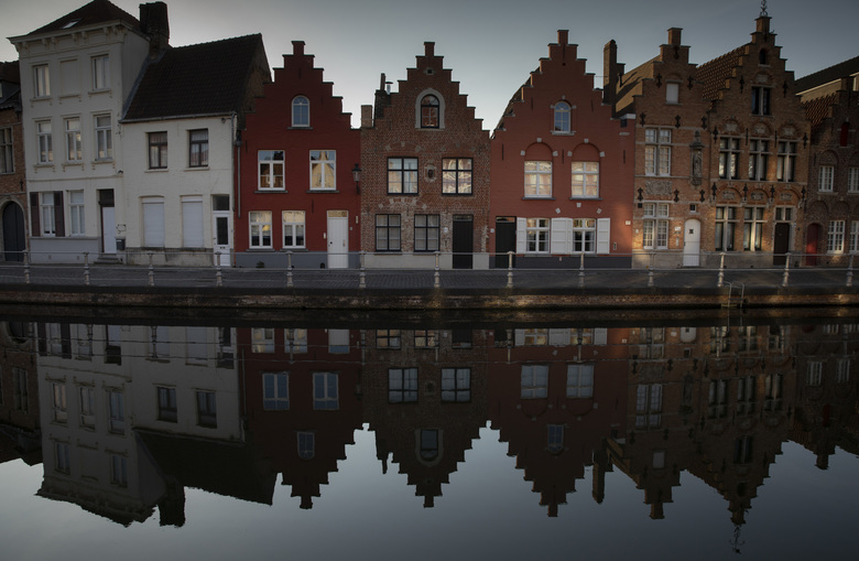 Houses make a reflection on the water in Bruges, Belgium, during a partial lifting of a lockdown to prevent the spread of coronavirus, COVID-19, Wednesday, May 13, 2020. Coronavirus lockdown restrictions have damaged the tourism industry in many European countries and left travelers wondering what restrictions will still be in place during the summer season. (AP Photo/Virginia Mayo)