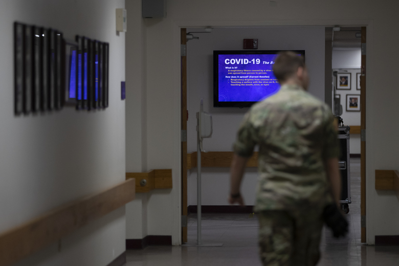 FILE – In this March 25, 2020, file photo a member of the U.S. Army walks down the hall toward a monitor displaying COVID-19 safety information in Fort Meade, Md. As of last week, the Army had already exceeded its retention goal of 50,000 soldiers for the fiscal year ending in September, re-enlisting more than 52,000 so far. (AP Photo/Carolyn Kaster, File)