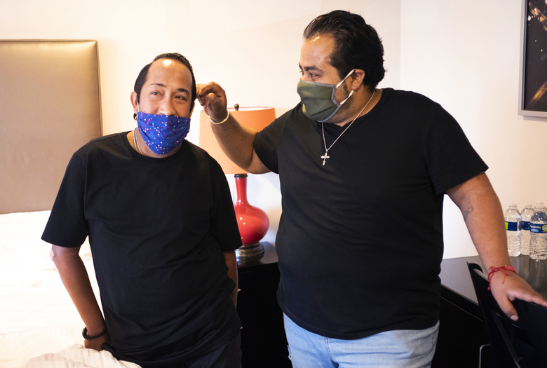 "Homeless couple, Matthew Padilla, left, and Juan ""Nito"" Padilla. Jr., pose for a photo at their room in a hotel in Los Angeles Thursday, May 14, 2020. Anxiety mounted every time someone at the homeless shelter sneezed or residents got too close. For Matthew Padilla, a 34-year-old with a pacemaker and asthma, catching the novel coronavirus would likely mean death. ""At the shelter I was constantly getting up, checking on him,"" said Nito Padilla, 36. ""And here I know he's safe. I know he's OK."" (AP Photo/Damian Dovarganes)"