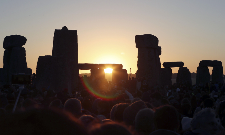 "FILE – In this June 21, 2019, file photo, the sun rises as thousands of revelers gather at the ancient stone circle Stonehenge to celebrate the Summer Solstice, the longest day of the year, near Salisbury, England. The coronavirus pandemic has scuttled summer solstice celebrations at Stonehenge, a highlight of the year for thousands of British pagans, druids and assorted revelers. English Heritage, which looks after the ancient stone circle, says restrictions on public events to slow the spread of the virus make it impossible to hold the event. It said it had decided to cancel the gathering ""after much deliberation and in consultation with our partners in the police and the emergency services, the druid and pagan community and others."" (AP Photo/Aijaz Rahi, File)"