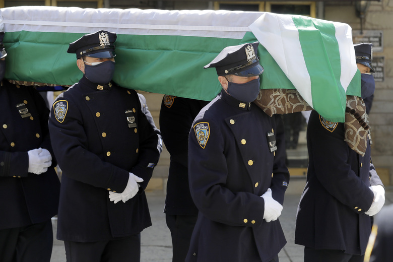 Members of the NYPD Honor Guard, wearing masks, carry the casket of Traffic Section Commander Mohammed Chowdhury during his funeral in New York, April 22, 2020. Chowdhury died on Sunday, April 19, 2020, from complications related to the new coronavirus. (AP Photo/Seth Wenig)