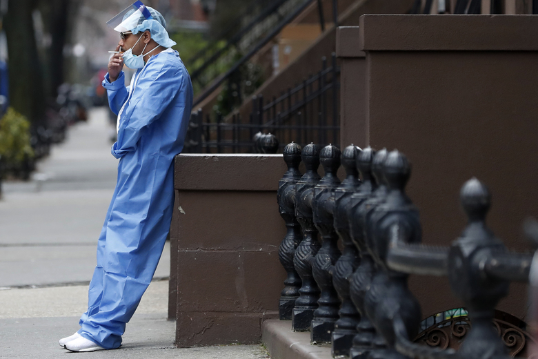 Emergency room nurse Brian Stephen leans against a stoop as he takes a break from his work at the Brooklyn Hospital Center, Sunday, April 5, 2020, in New York. (AP Photo/Kathy Willens)