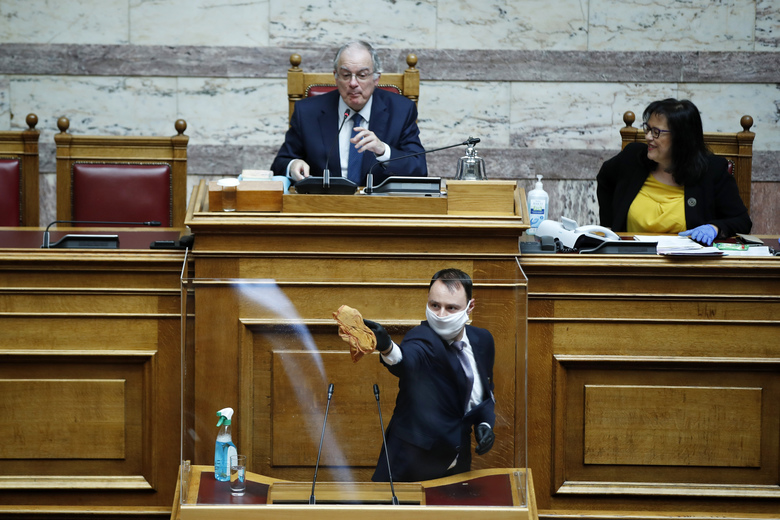 FILE – In this Thursday, April 30, 2020 file photo, an employee of the Greek parliament, wearing a face mask to protect from the coronavirus, cleans a protective plastic shield in Athens. Across Europe and beyond, parliaments and governments have had to adapt their operations to stop the virus spreading through the corridors of power. Social distancing, online debates, masks, plexiglass, hazard tape, each country's legislature has its own measures. (AP Photo/Thanassis Stavrakis, File)